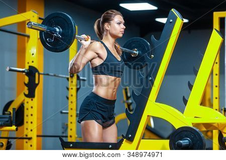 Photo Of A Woman Holding Weight While Working Out With Barbell In A Gym. Muscles Woman Showing Sixpa