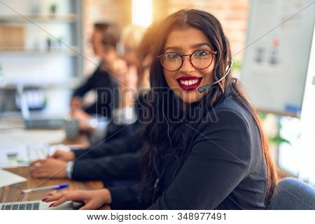 Group of call center workers working together with smile on face using headset. Young beautiful woman smiling at the office.