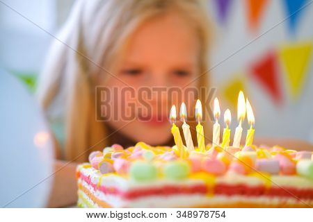 Blonde Caucasian Little Girl Looking At Candles On Birthday Rainbow Cake, Making A Wish Before Blows