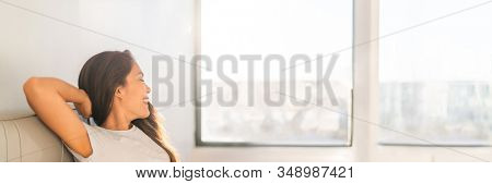 Clean indoor air happy Asian woman breathing at home from air purifier sitting in sofa looking out the window panoramic banner.