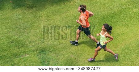 Run jog couple athletes training together doing running workout partner buddy jogging on green grass park lawn top view from drone. Asian woman and man runners.