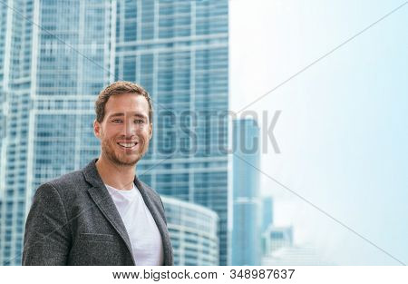 Confident young business man in smart casual blazer jacket portrait outdoor in city skyscrapers highrise buildings background. Male caucasian model in his 30s.