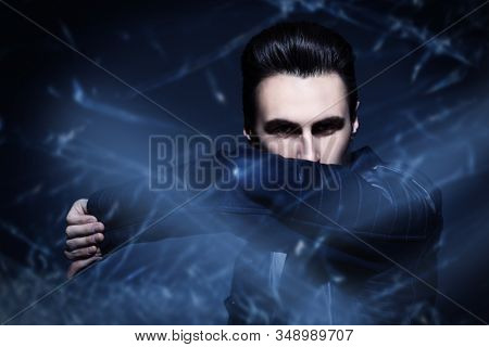 Men's fashion. Portrait of a handsome man in black leather jacket staring intently at the camera. Studio portrait.