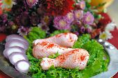 Raw chicken legs arranged with fresh salad, aromatic spices onions and flowers on a silver plate poster