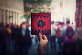 Hand Holds Red Banner Warning Rapidly Spreading Coronavirus On Crowded City Streets. Deadly Corona V