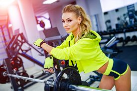 Pretty Woman Or Cute Girl With Sexy Body In Yellow Training Clothes In Sport Gym Near Metallic Barbe