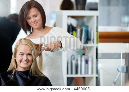 Mirror reflection of hairdresser giving a haircut to woman at parlor
