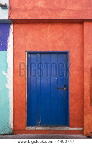 Small Blue Door Surrounded By Orange