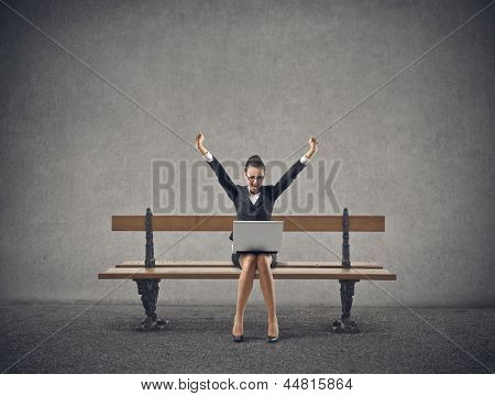 happy businesswoman sitting on a bench with laptop