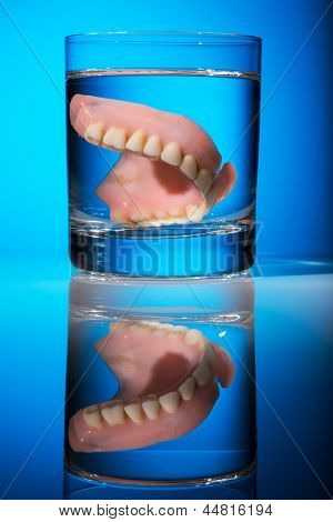 a denture is cleaned in a glass of water. proper hygiene.
