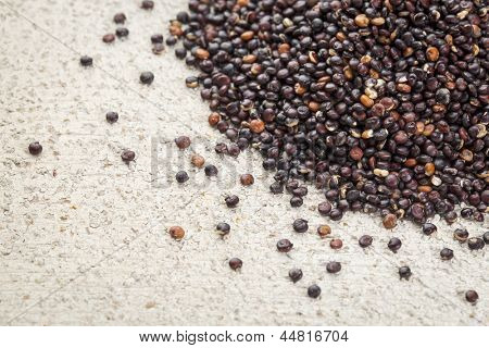 black quinoa grain grown in Bolivia on rough white painted barn wood background