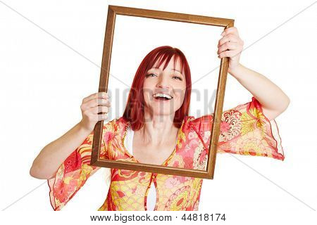 Happy best ager woman holding empty picture frame in front of her face