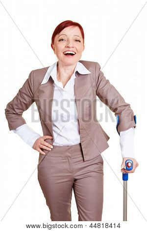 Happy best ager business woman standing with crutches
