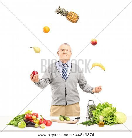 A smiling mature man juggling fruits behind a table full with ingredient, isolated on white background