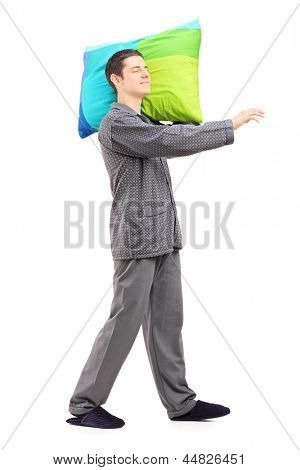 Full length portrait of a man sleepwalking and holding a pillow, isolated on white background