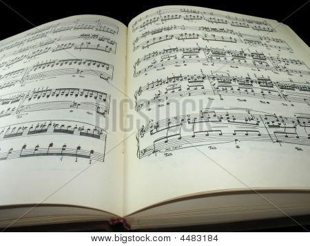 Old Vintage Sheet Music Book Over Black Background