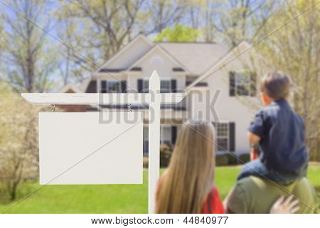 Mixed Race Young Family in Front of Blank Real Estate Sign and New House - Ready for Your Text.