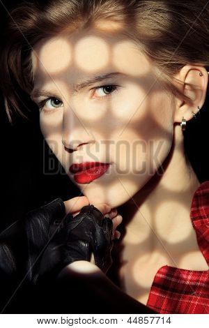 Portrait of a young fashionable model posing at studio with expression. Black background. poster