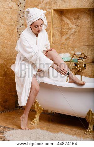 Woman Shaving Her Legs In Bathroom.