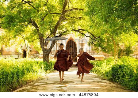 Two little monks running outdoors