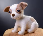Toy dog, hand made puppy sitting in studio on wooden stool, felting poster