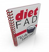 A spiral-bound book with the words Diet Fad - It's the Latest Craze to illustrate a new dieting sensation inside a best-selling manual or guide to help you lose weight poster