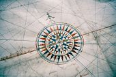 Old compass on vintage map. Shallow depth of field with focus on the compass. poster