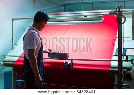 Indonesian textile worker in a manufacturing plant controls the quality of a fabric roll and logs any faults