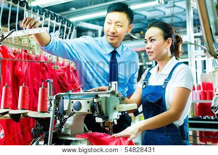 Seamstress is new assigned to a machine in a textile factory, the foreman explains something
