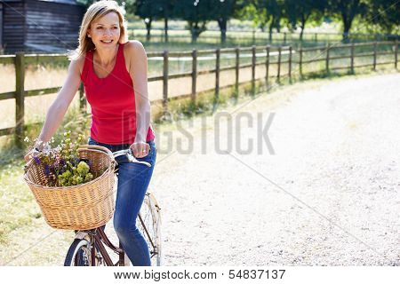 Attractive Woman Riding Bike Along Country Lane poster