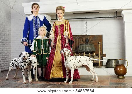 Father, mother and son in colorful medieval costume stand near fireplace with three dalmatians on leashes.