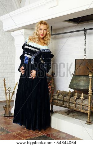 Cute woman in medieval costume poses near fireplace and smiles.