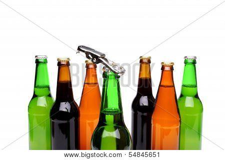 Opener on bottleneck. Bottles of beer. Close up.