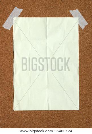 Blank Beige Paper Stuck To A Cork Noticeboard.