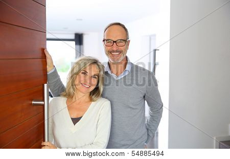 Senior couple welcoming people to enter home