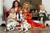Happy father, mother, little daughter and two sons in medieval costumes sit with two dalmatians near fireplace. poster