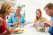 Family With Teenage Children Eating Meal At Home Together poster