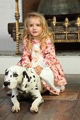 Happy pretty little girl in medieval costume sits with dalmatian near fireplace. poster
