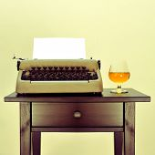 an old typewriter with a blank page and a brandy snifter with liquor on a desk, with a retro effect poster