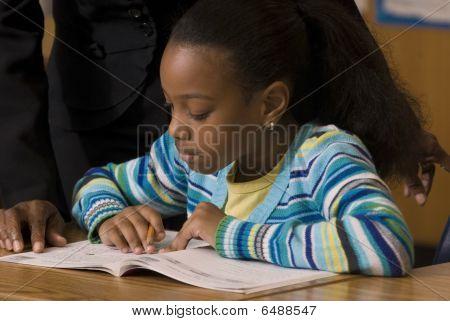 Student Works In Workbook During School