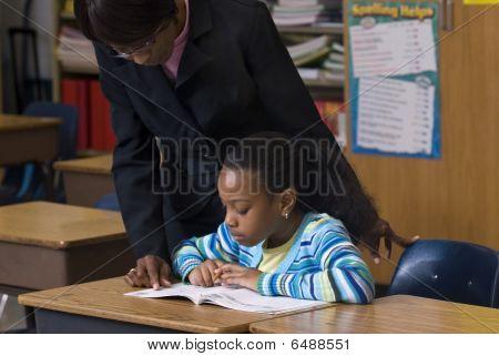 Teacher Looking Over Student Shoulder