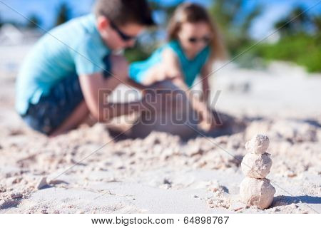 Sandman build from exotic pink sand with two kids building sandcastle on background while on beach holidays