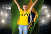 Excited football fan in brasil tshirt holding brasil flag against large football stadium with fans in blue poster