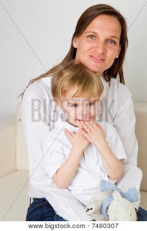 Young boy is sitting on his mothers lap poster