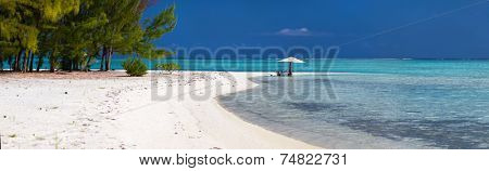 Panoramic photo of a table set on deserted tropical beach for an exotic picnic