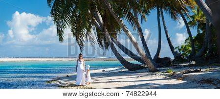 Panorama of mother and daughter on a deserted tropical beach