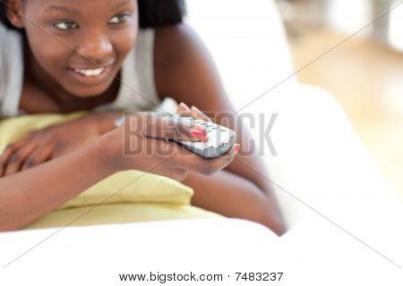 リビング ルームでテレビを見て若い女性