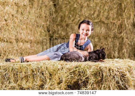 Bavarian girl playing with cat on hayloft