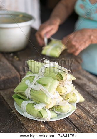 Woman making tamales in Cuba the tamal is a traditional Mesoamerican dish made of masa which is steamed or boiled in a leaf wrapper. poster