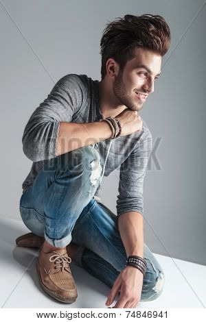Full body picture of a young fashion man relaxing on the floor while smiling and looking away from the camera.